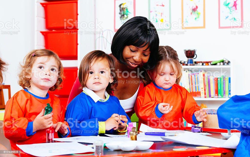 Group Of Little Children Enjoying Art And Craft At Nursery stock photo