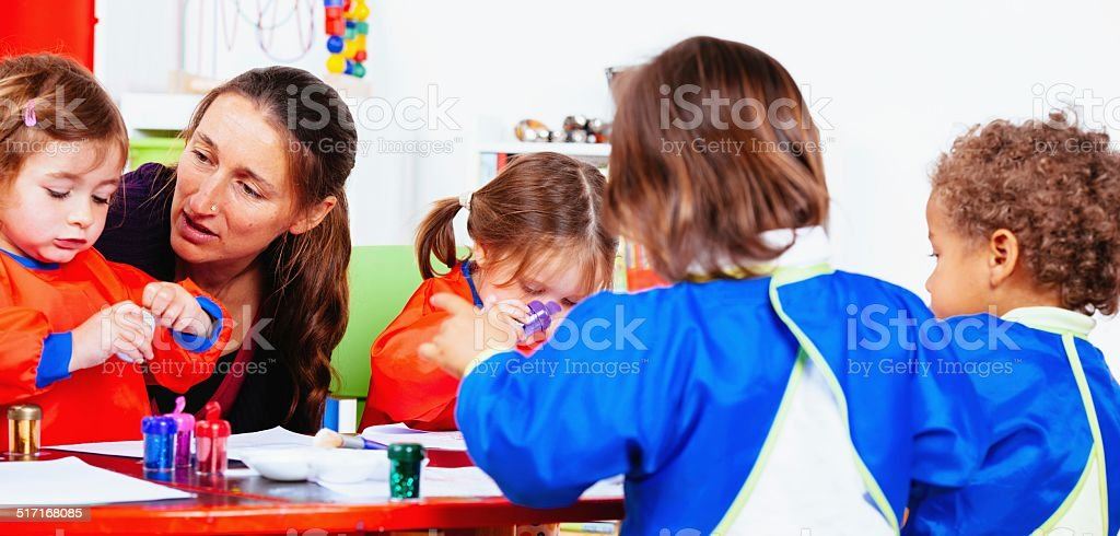 Group Of Little Children Enjoying Art And Craft With Carer stock photo