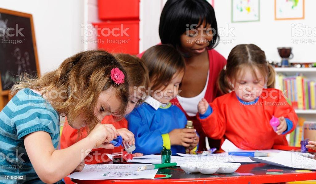 Group Of Little Children Enjoying Art  With Their Teacher/ Carer stock photo