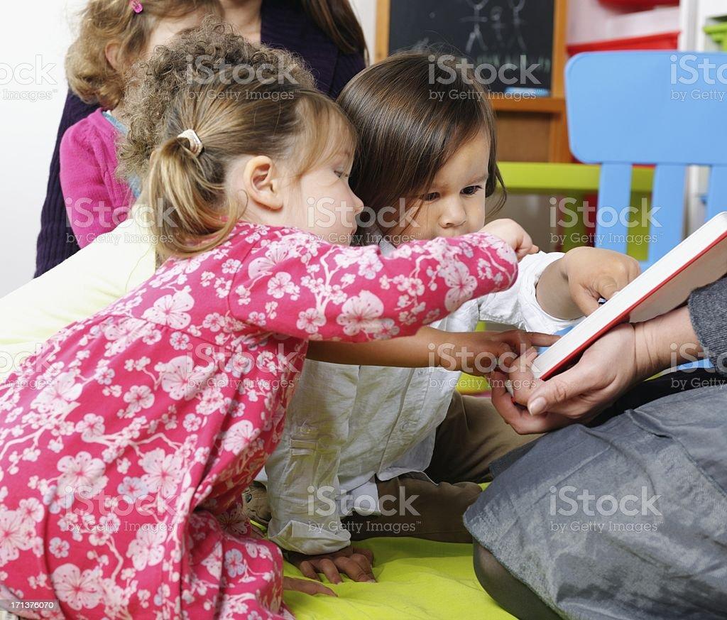 Group Of Little Children Enjoying Interactive Storytime stock photo