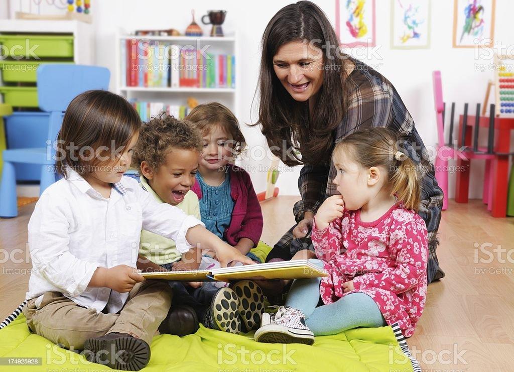 Group Of Little Children Enjoying Storytime In A Nursery Setting stock photo