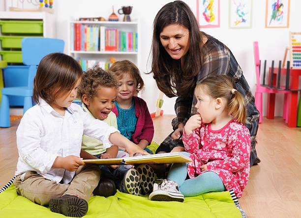Gruppe von kleinen Kindern genießen Geschichtenerzählen im Kinderzimmer Ambiente – Foto