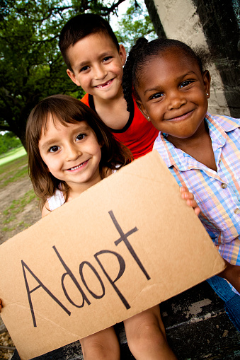 Group Of Little Children Holding Sign Reading Adopt Stock Photo - Download Image Now