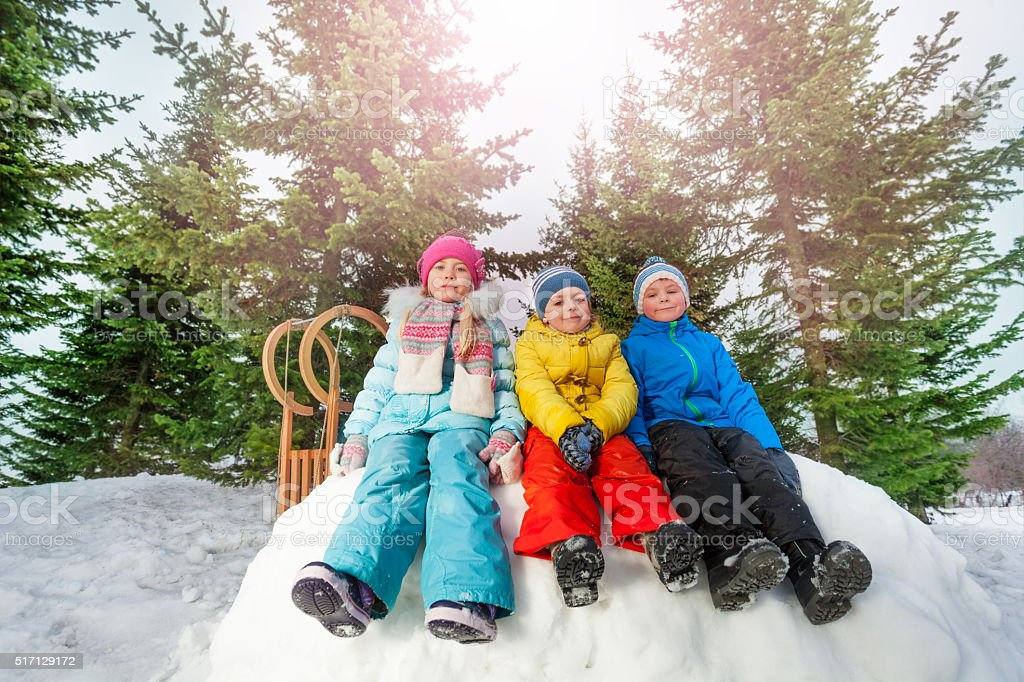 Group of little children sit on snow wall in park stock photo