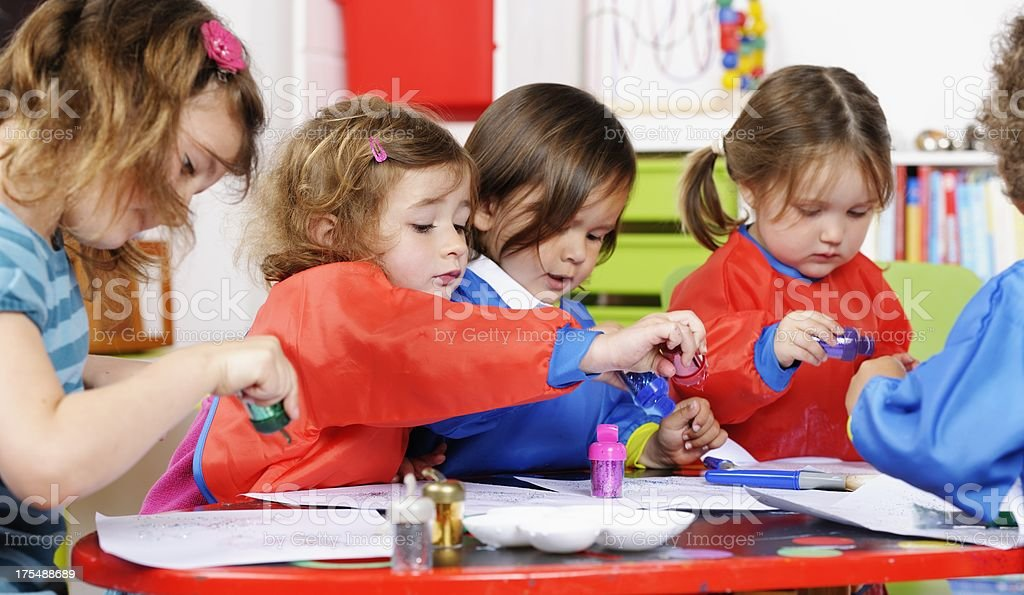 Group Of Little Children Using Glitter To Create Art royalty-free stock photo