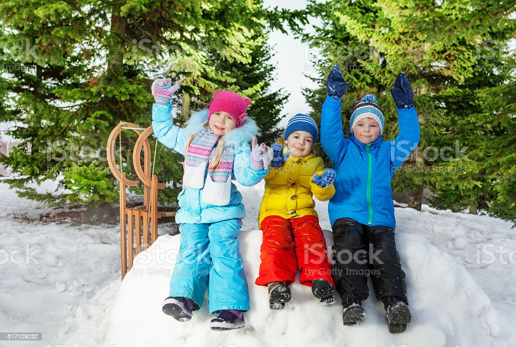 Group of little kids sit on snow wall in park stock photo