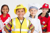 group of happy kids dressing in various occupational workers uniforms