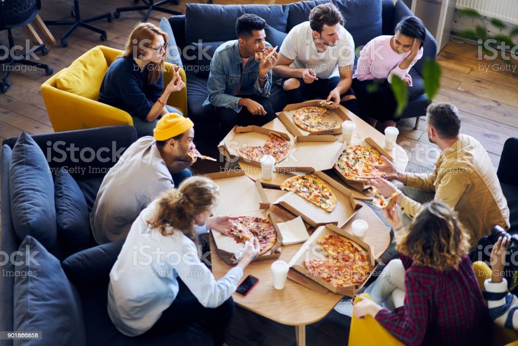 Group of male and female coworkers having  lunch break eating pizza together in office, overhead shot of young casually dressed staff members recreating after finishing tasks making fast snack stock photo