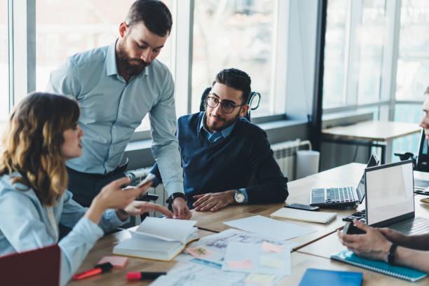 gruppe von männlichen und weiblichen fachleuten in formeller kleidung, die miteinander kommunizieren und businessplan für die entwicklung von design-projekt während kollaborativer prozess in modernen büro diskutieren - geschäftsstrategie stock-fotos und bilder