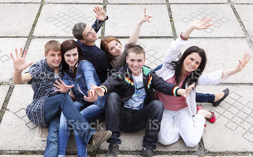 Group of male and female students sitting on street royalty-free stock photo