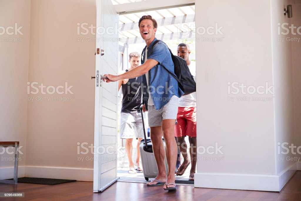 Group Of Male Friends Arriving At Summer Vacation Rental royalty-free stock photo