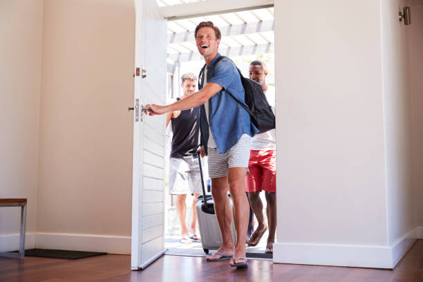 Group Of Male Friends Arriving At Summer Vacation Rental stock photo