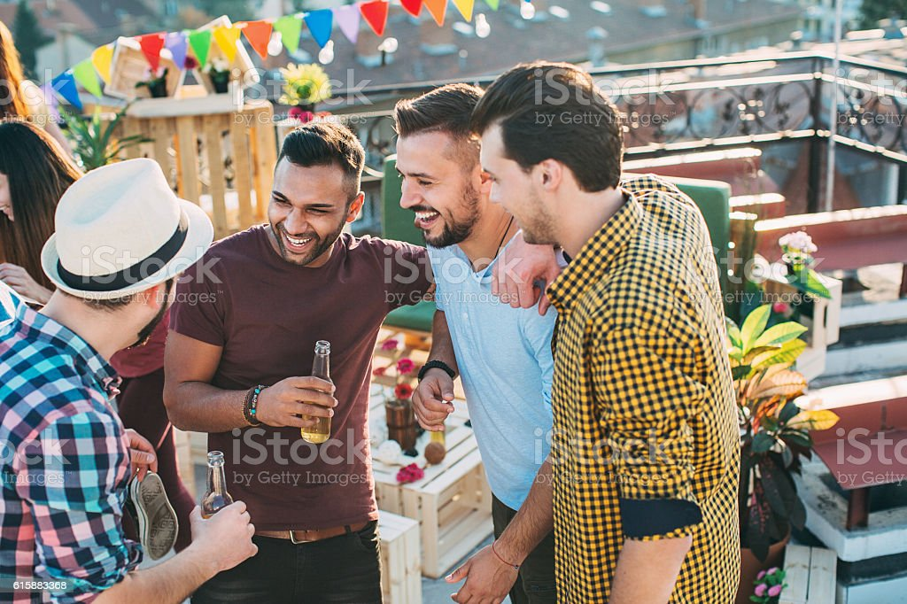 Group of male friends chatting and drinking stock photo