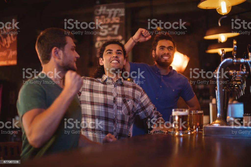 Group of male friends watching football match stock photo