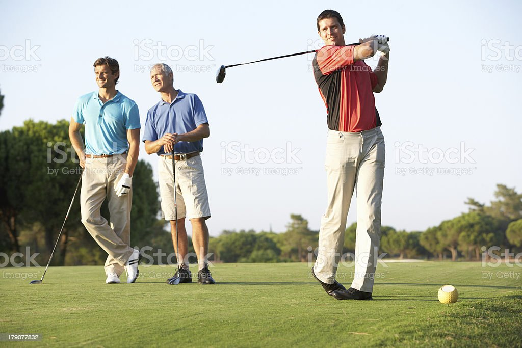 Group Of Male Golfers Teeing Off On Golf Course stock photo