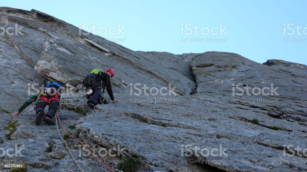 group of male rock climbers on a hard north face climbing route in the Alps stock photo