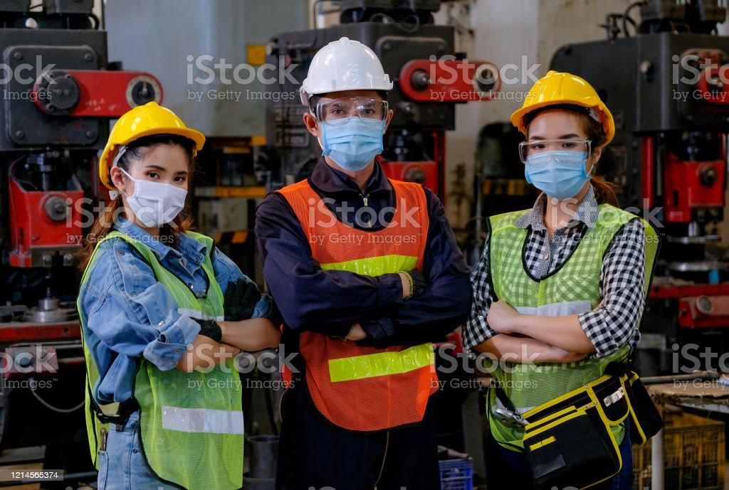 Grupo de trabalhadores homens e mulheres com máscara estão com ação confiante no local de trabalho da fábrica e várias máquinas como fundo - Foto de stock de Adulto royalty-free