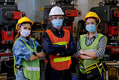 istock Group of man and woman workers with mask stand with confident action in the factory workplace and various machine as background 1214565374