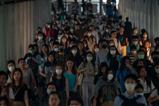 gruppe von vielen gehalt mann mit gesichtsmaske für schützen mikro staub in luft und gehen zu ihrem arbeitsplatz während der pm2, 5 luftverschmutzung krise in bangkok an der hauptverkehrszeit moring. - hochbahn passagierzug stock-fotos und bilder