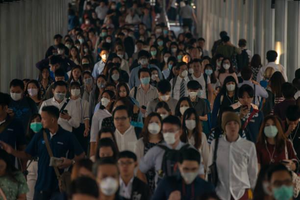 顔のマスクを身に着けている多くのサラリーマンのグループは、朝ラッシュ時バンコクで pm2.5 大気汚染危機中に職場に通いながら空気で微細塵を保護します。 - マスク ストックフォトと画像