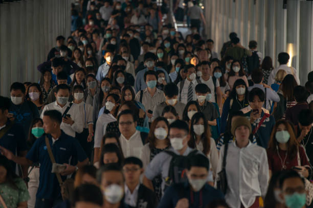 group of many salary man wearing face mask for protect micro dust in air while going to their workplace during pm2.5 air pollution crisis in bangkok at moring rush hour. - mask stock pictures, royalty-free photos & images