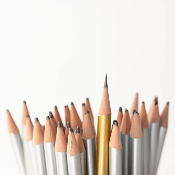 Group of many silver colored pencils being blunt but one golden pencil higher than the rest being super sharp standing out from the crowd. stock photo