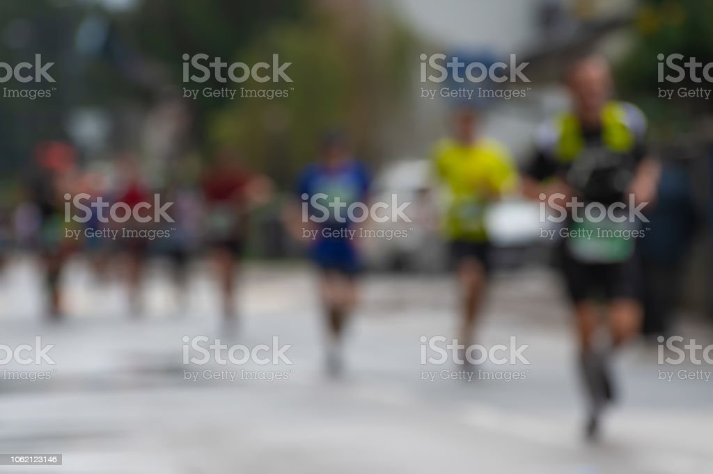 Blurred photograph of a group of marathon racers running on a rainy...