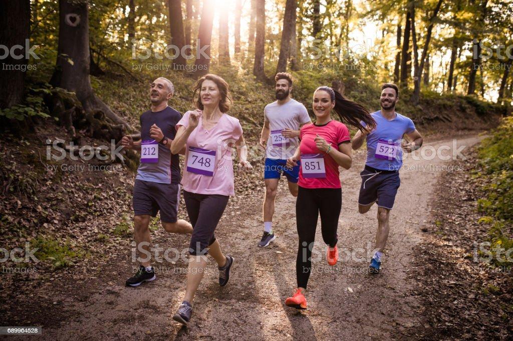 Grupo de corredores de maratona, correndo por uma trilha na floresta. - foto de acervo