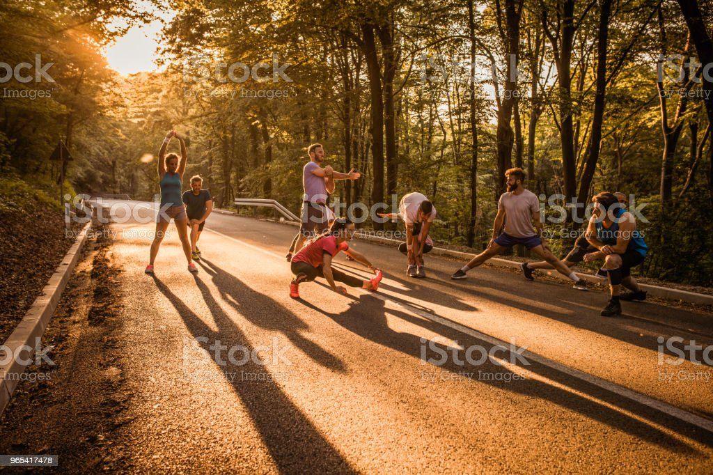 Group of marathon runners warming up on a road at sunset. royalty-free stock photo