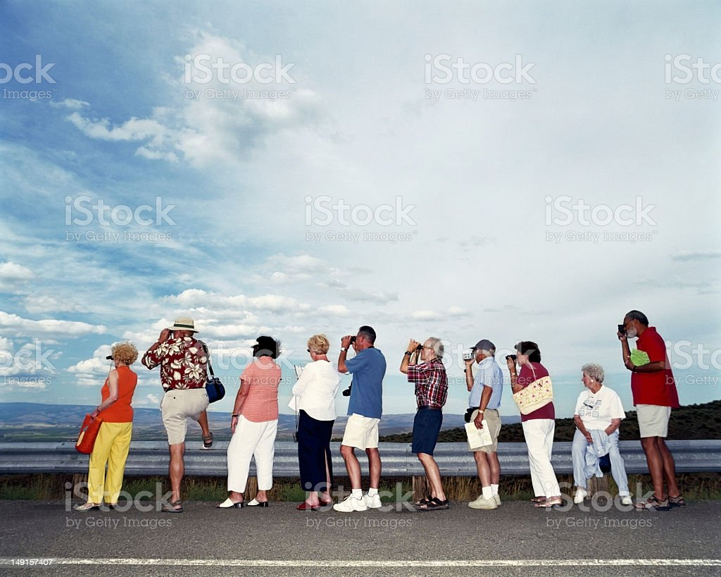Group of mature adults using binoculars and cameras stock photo