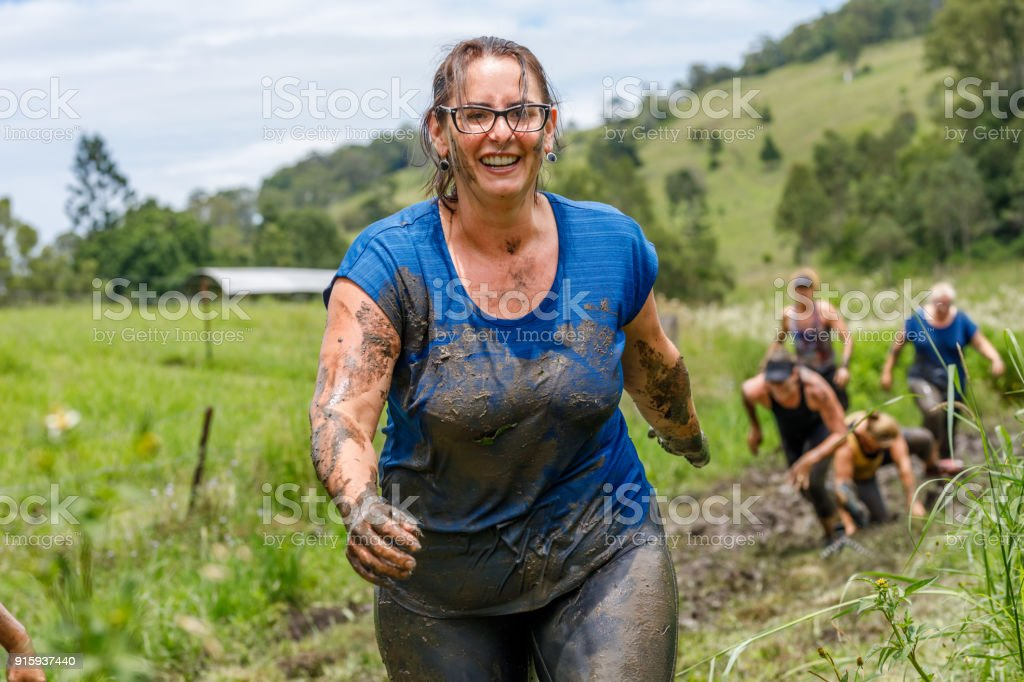 Group Of Mature Age Women Participating In Mud Run Fitness Training Together stock photo