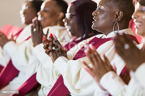 A group of mature black women in church robes, sitting in a row, clapping. They are members of the church choir listening to a sermon.