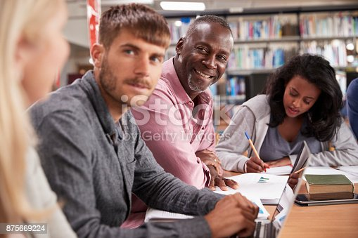 877026364 istock photo Group Of Mature College Students Collaborating On Project 875669224