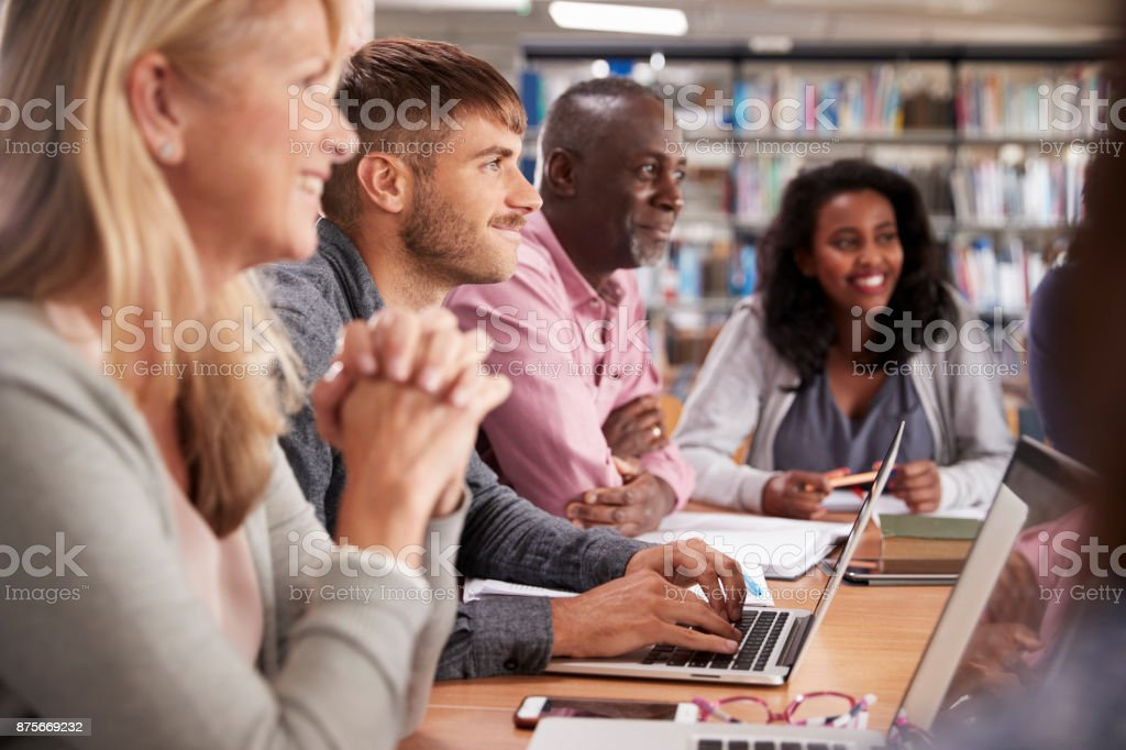 Group Of Mature College Students Collaborating On Project stock photo