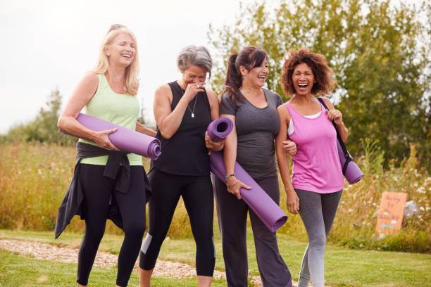 gruppe von reifen weiblichen freunden auf outdoor yoga retreat zu fuß auf dem weg durch den campingplatz - freundin stock-fotos und bilder