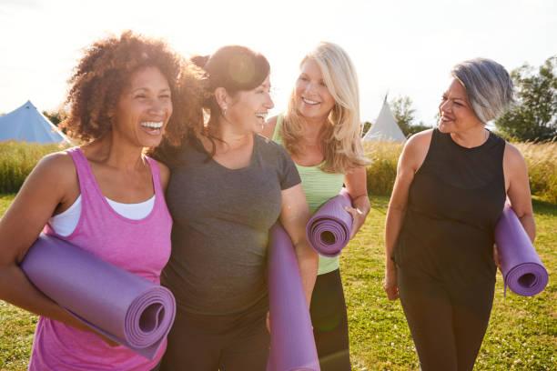一群成熟的女性朋友在戶外瑜伽撤退沿著路徑通過營地散步 - 健康的生活方式 個照片及圖片檔
