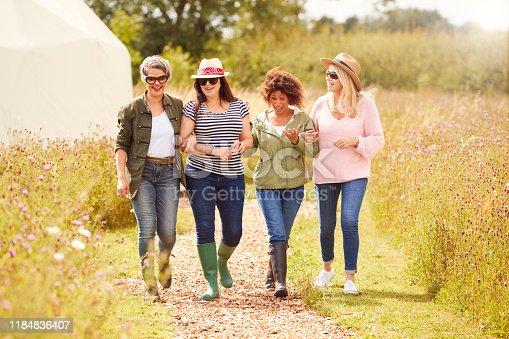 Group Of Mature Female Friends Walking Along Path Through Yurt Campsite