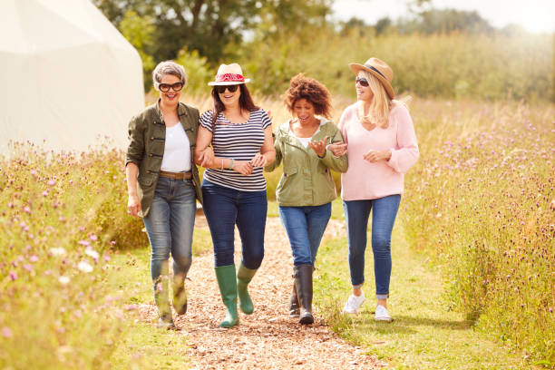 Group Of Mature Female Friends Walking Along Path Through Yurt Campsite stock photo
