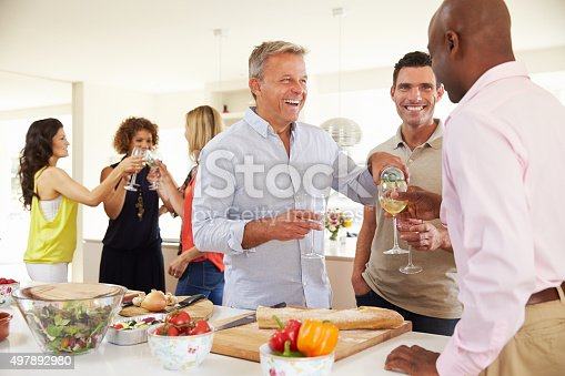 istock Group Of Mature Friends Enjoying Dinner Party At Home 497892980