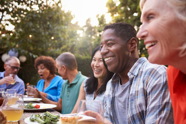 group of mature friends enjoying outdoor meal in backyard - party social event stock pictures, royalty-free photos & images