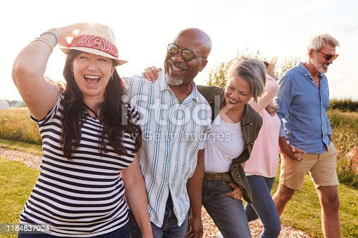 Group Of Mature Friends On Vacation Walking Along Path Through Campsite At Sunset