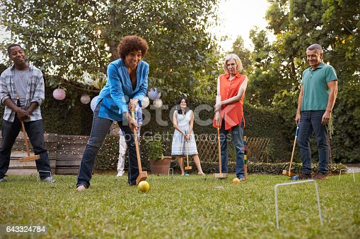 istock Group Of Mature Friends Playing Croquet In Backyard Together 643324784