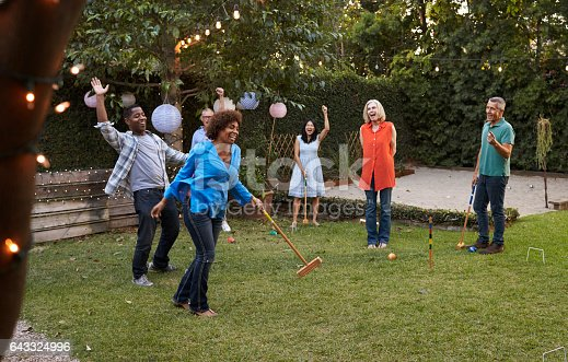 istock Group Of Mature Friends Playing Croquet In Backyard Together 643324996