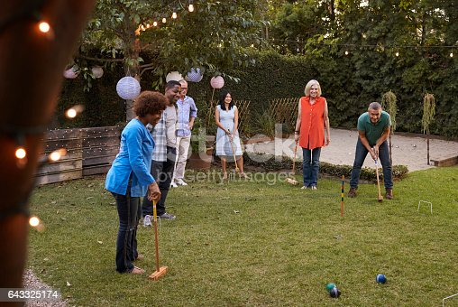 643325030 istock photo Group Of Mature Friends Playing Croquet In Backyard Together 643325174