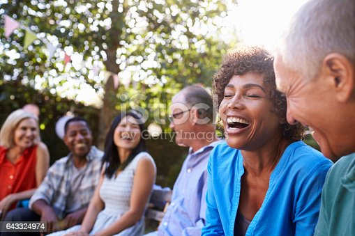 istock Group Of Mature Friends Socializing In Backyard Together 643324974