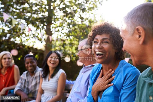 643325030 istock photo Group Of Mature Friends Socializing In Backyard Together 643325030