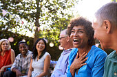 istock Group Of Mature Friends Socializing In Backyard Together 643325030