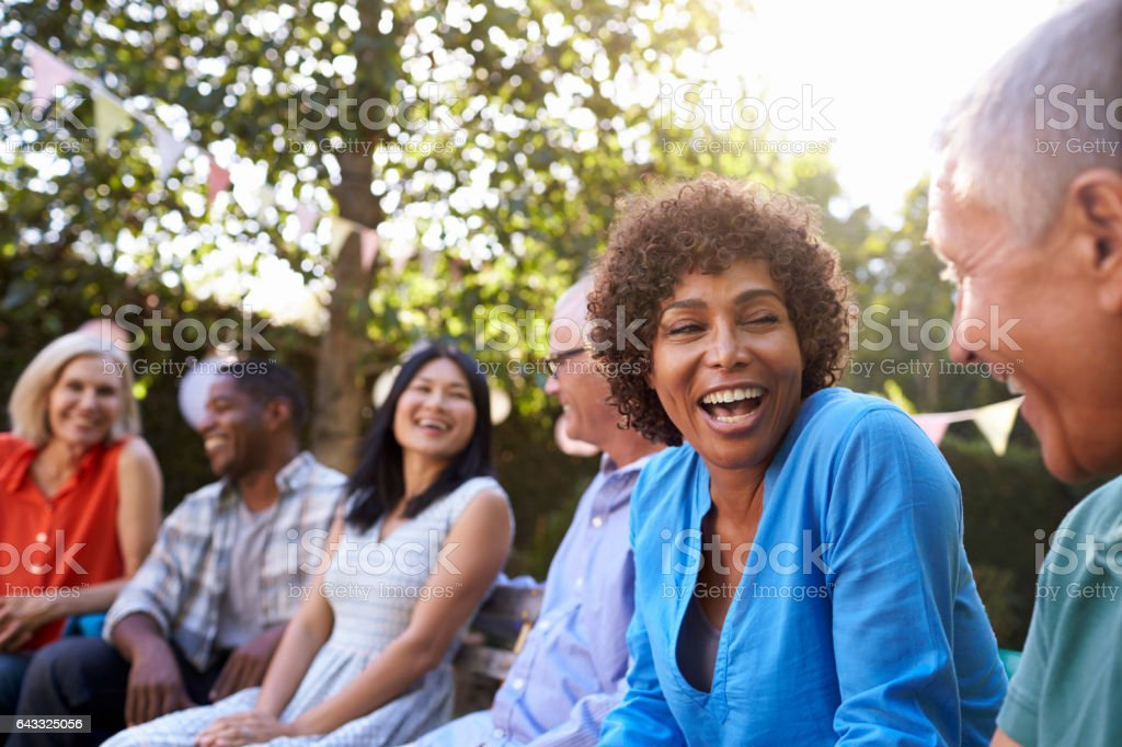 Group Of Mature Friends Socializing In Backyard Together stock photo