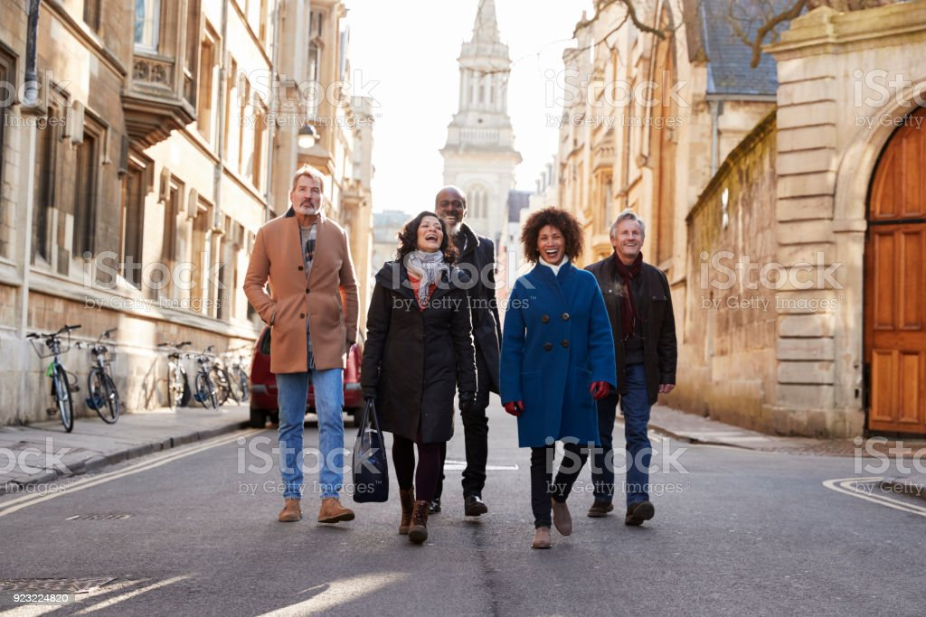 Group Of Mature Friends Walking Through City In Fall Together stock photo