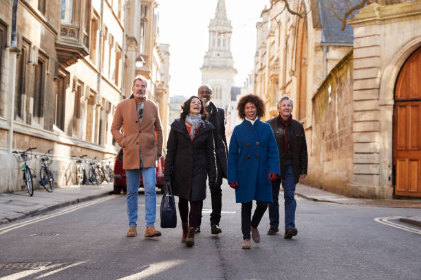 group of mature friends walking through city in fall together - tourism stock pictures, royalty-free photos & images